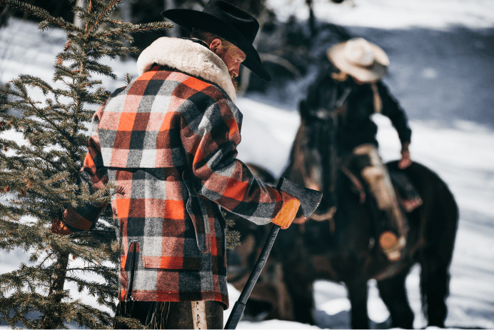 Filson Lined Wool Packer Coat in black, charcoal, and rust plaid worn on man working in the snowy woods with person on horse in background