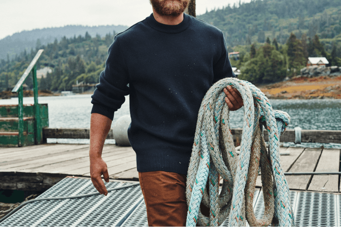 Filson Cotton Guide Crew Neck Sweater color Navy worn on Man working on fishing dock holding large braided rope