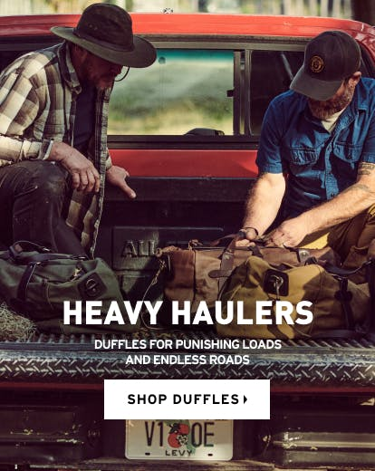 Image of men in back of truck/Heavy Haulers/Duffles for punishing roads/and endless roads/shop duffles