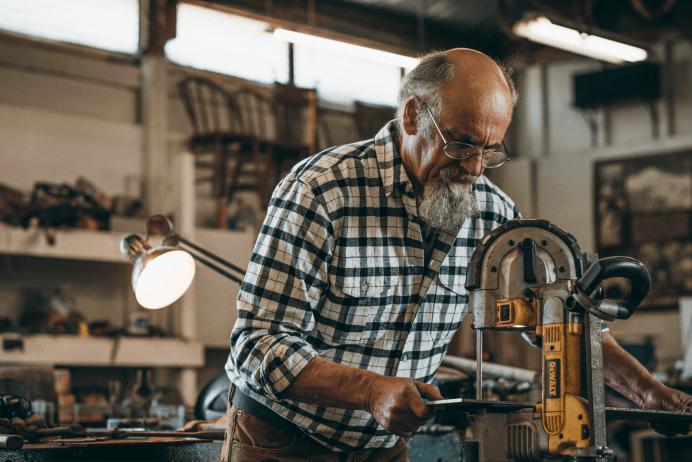 Filson Alaska Guide Shirt Color Cream and Black Plaid on Gentleman in Workshop Utilizing Large Machinery