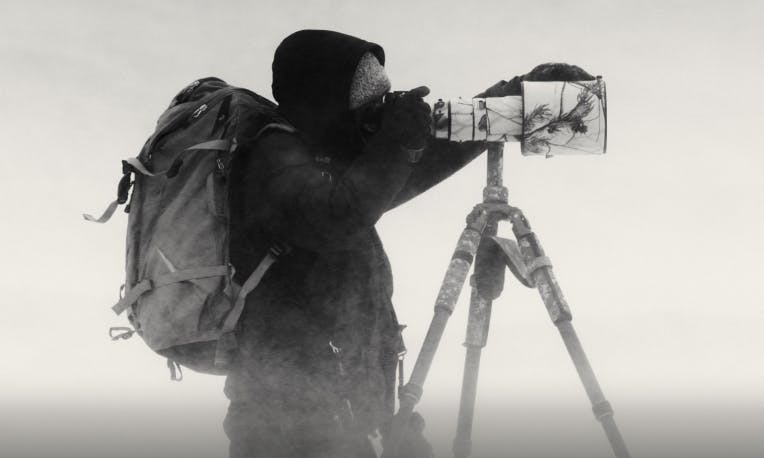 Man standing in artic conditions wearing heavy Filson coat and backpack holding a camera/Kiliii Yuyan/profiles from the field/a fire inside: extreme cold-weater photography/read now