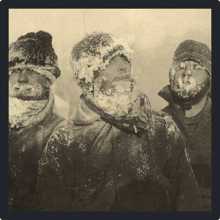 Three men standing should-to-shoulder with their faces covered in snow and frost