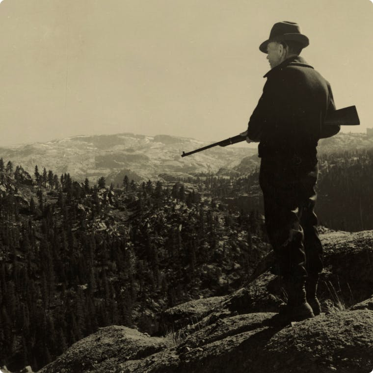 Man standing on mountaintop overlooking forests and distant mountains